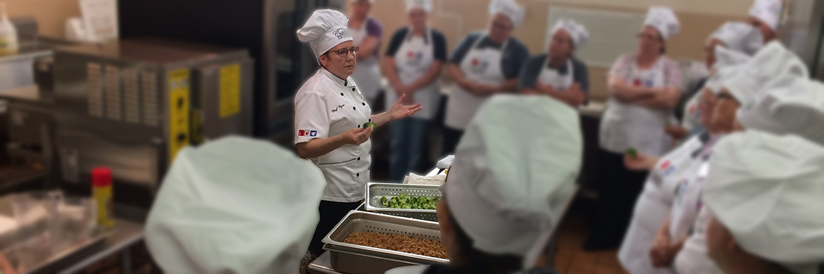 chef teaches a culinary course in school kitchen